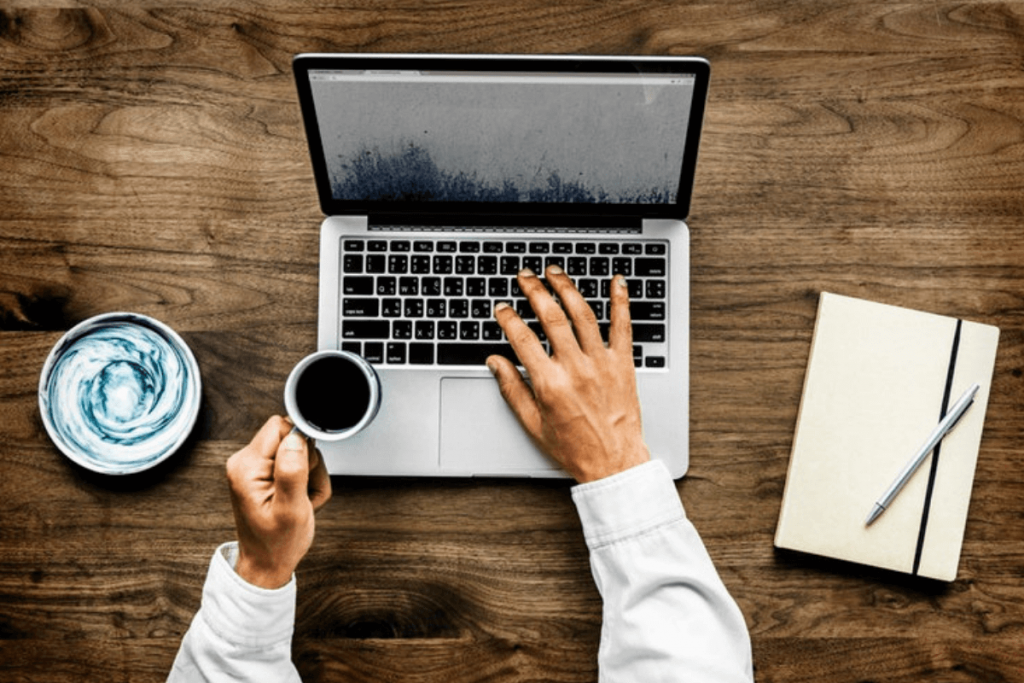 Man using a laptop while holding coffee
